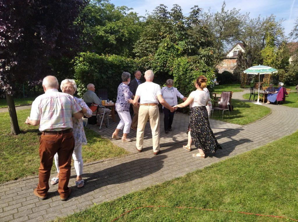 Uczestnicy Dziennego Domu Pomocy w Koninie tańczą na  świeżym powietrzu.