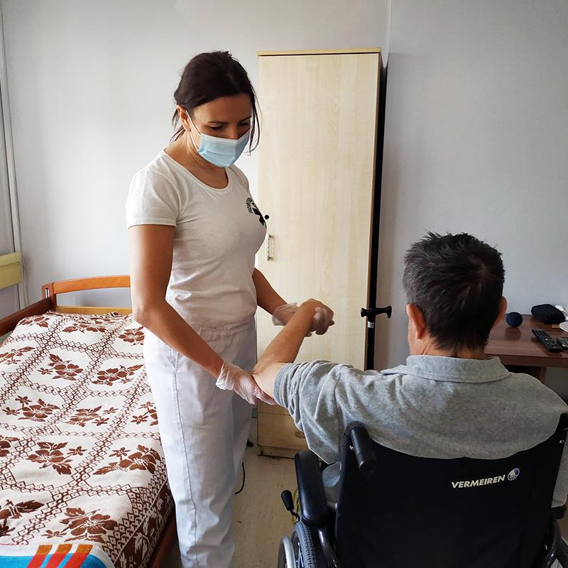 Fizjoterapeutka ćwiczy z mieszkańcem Domu Pomocy Społecznej w Koninie