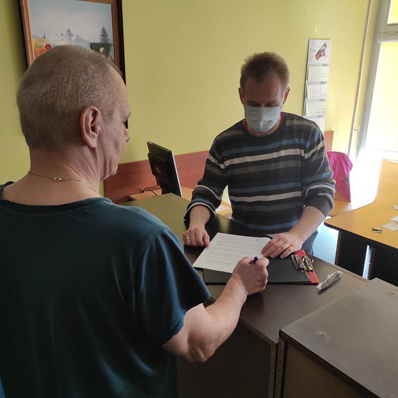Pracownik socjalny wypełnia dokumenty z mieszkańcem DPS Konin
