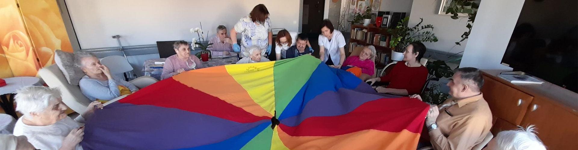 terapia zajęciowa - mmieszkańcy domu pomocy społecznej w Koninie bawią się chustą