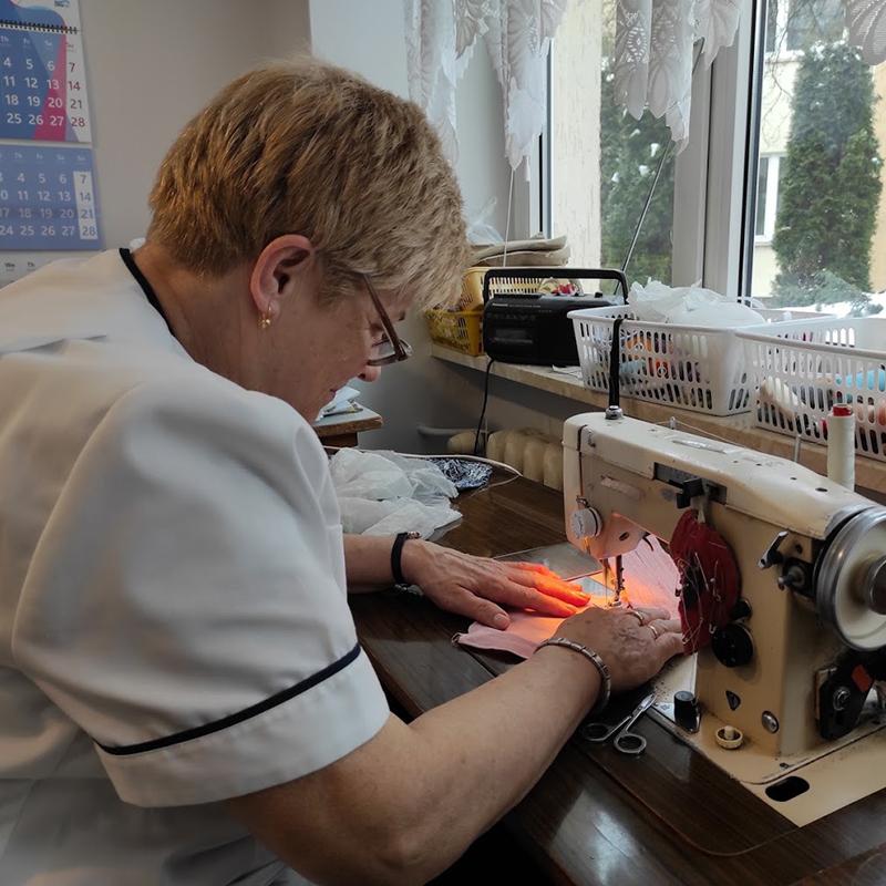 Krawcowa w Domu Pomocy Społecznej w Koninie naprawia odzież mieszkańców