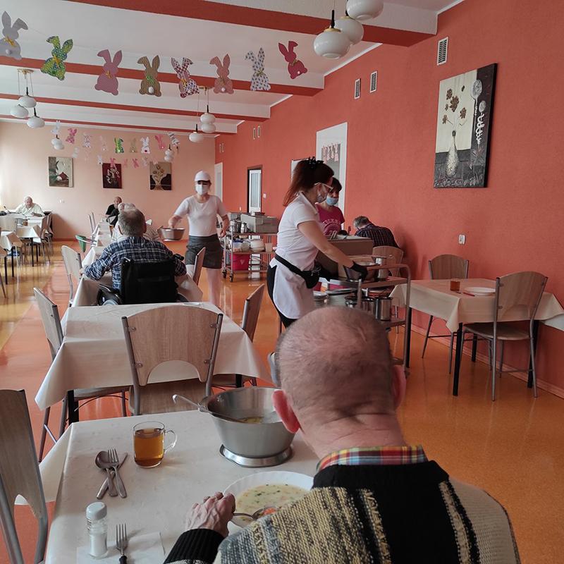 Mieszkańcy dps  jedzą posiłek na stołówce. Panie opiekunki na specjalnych wózkach wiozą przygotowany posiłek dla mieszańców leżących